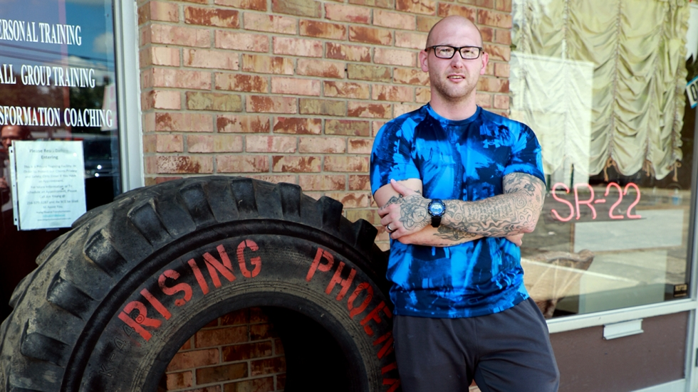 Jonathan Young poses in front of his gym beside a large tire reading Rising Phoenix Transformations in Northfield, Ohio.