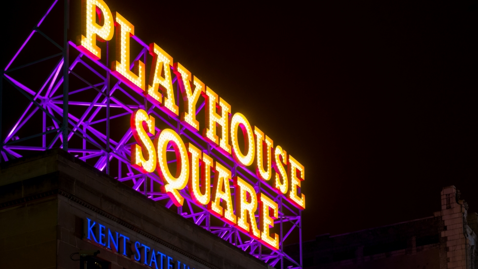 The Playhouse Square sign glows in yellow and purple on top of a building in the district