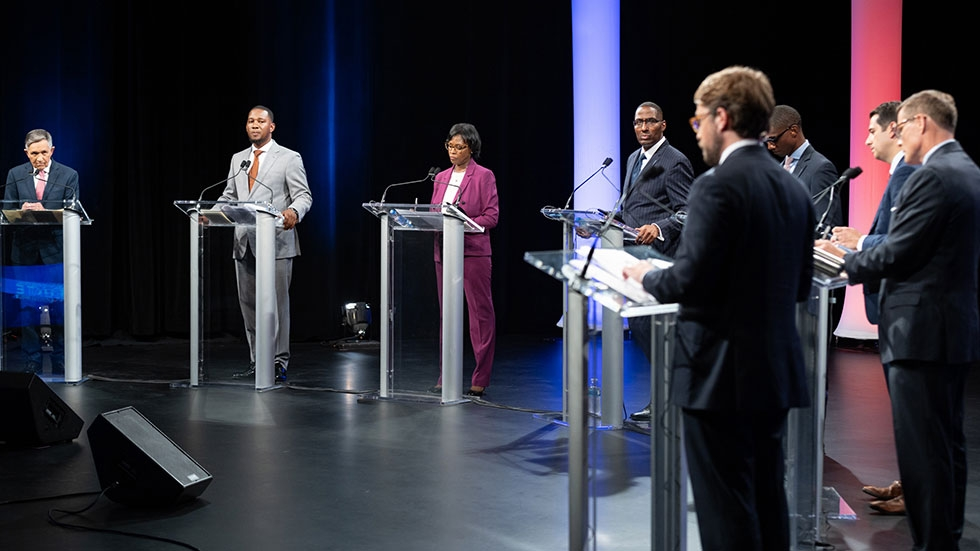 Seven Cleveland mayoral candidates stand at podiums at the Idea Center in Cleveland's Playhouse Square.