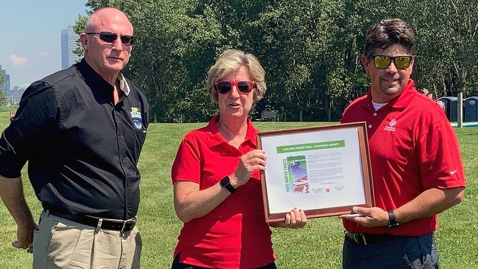 From left to right, ODNR Chief of the Division of Parks and Watercraft Glenn Cobb, ODNR Director Mary Mertz and Cleveland Metroparks CEO Brian Zimmerman hold to official water trail designation.