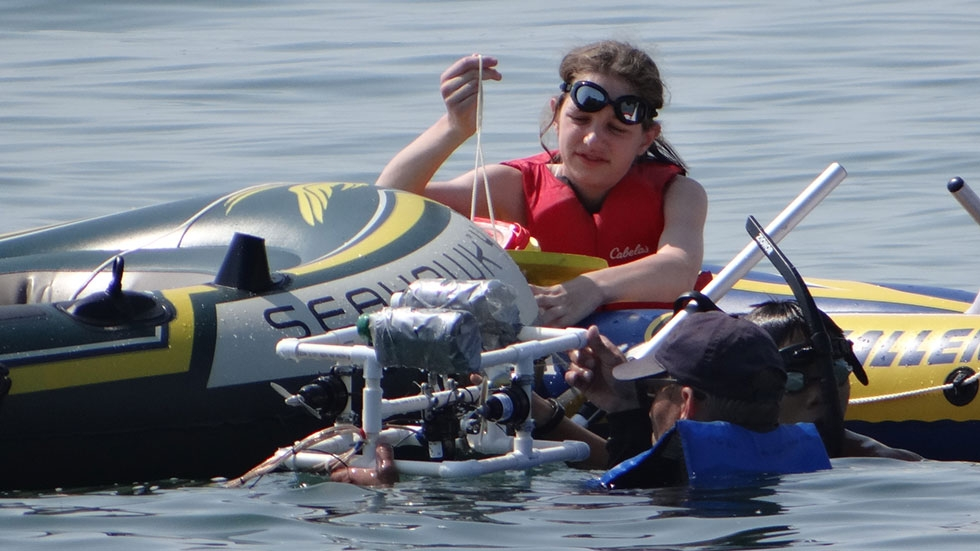 A student in a raft and a teacher in the water at Lake Erie with a remotely operated vehicle carrying an underwater camera