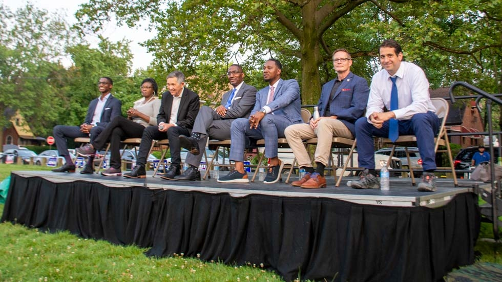 Justin Bibb, Sandra Williams, Dennis Kucinich, Zack Reed, Basheer Jones, Kevin Kelley and Ross DiBello sit on a stage at a candidate forum in Cleveland, Ohio.