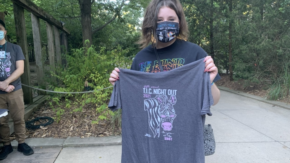 Christie London, a 13-year-old from Akron, shows off a shirt she designed for the annual TIC Night Out at the Akron Zoo, put on by Akron Children's Hospital. London has Tourette syndrome and participated in a behavioral therapy program at the hospital. [Anna Huntsman / Ideastream Public Media]