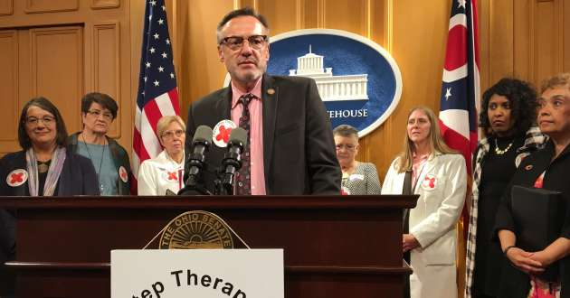 """Scott Lipps (R-Franklin, center) talks about his experience as """"step therapy"""" bill sponsors Rep. Nickie Antonio (D-Lakewood, far left), Sen. Peggy Lehner (R-Kettering, second from left) and Sen. Charleta Tavares (D-Columbus, far right) look on."""