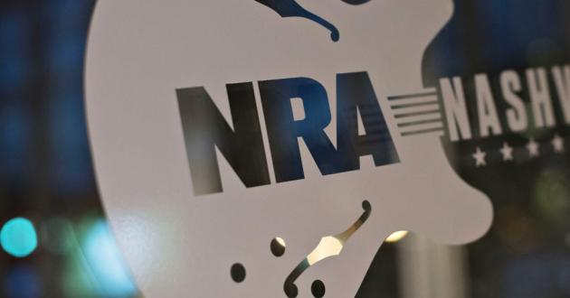 A sign touts the 144th National Rifle Association annual meetings and exhibits. One of the groups the student is said to have infiltrated is a gun rights organization, that NPR has previously identified as the National Rifle Association.