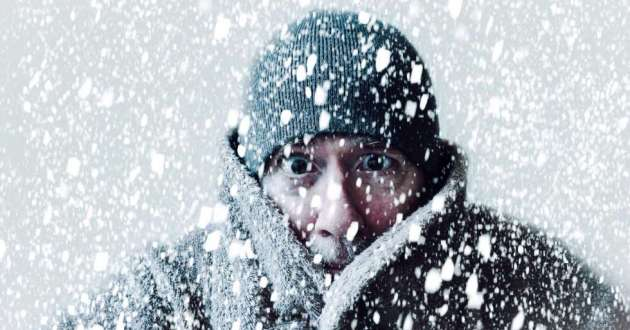 A man bundled up in a hat and coat looks like he is freezing as snow falls around him.