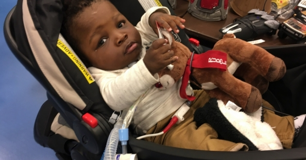 1 1/2-year-old Isaiah Crittenden lies in his stroller at the RePlay for Kids adapted toys giveaway.