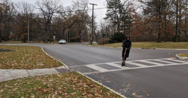 A person in a dark overcoat on a scooter drives over a new pedestrian crosswalk and through the narrower intersection of Edgehill and Overlook roads following Complete Streets improvements.