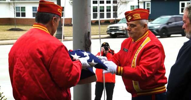 Two Marine Corps League members fold an American flag during the ceremony in Fairview Park to honor James Patrick Witt.