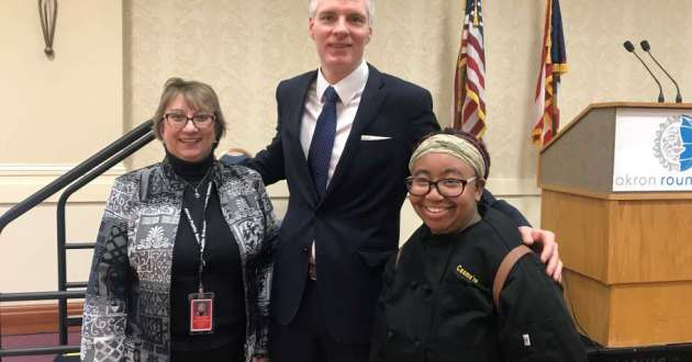 Edwin's Restaurant owner Brandon Chrostowski visited briefly with Buchtel HS culinary students and their teacher after his Akron Roundtable address at Quaker Station. He paused for a photograph with senior Cashmere Peterson.