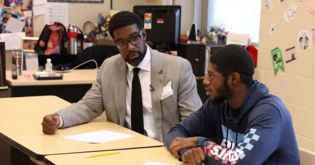 East Cleveland schools CEO Henry Pettiegrew visits a class at Shaw High School and participates in the discussion with a student about U.S. government.