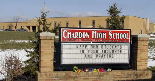 Bouquets of flowers sit on the sign in front of the high school in Chardon, Ohio Tuesday, Feb. 28, 2012, days after a gunman killed three students at the school.
