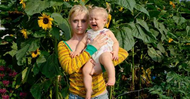 A young woman holds a baby in front of sunflowers.
