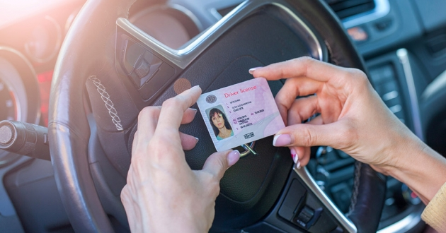 A woman sitting in the driver's seat holds up a driver's license next to her steering wheel.