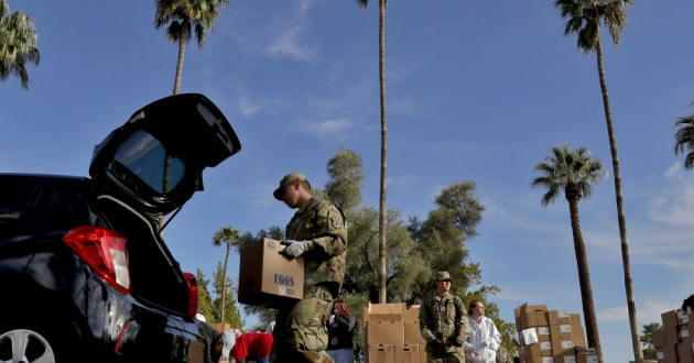 Members of the Arizona National Guard distribute food on March 27 in Mesa, Ariz. The Guard has been activated to bolster the supply chain and distribution of food amid surging demand in response to the COVID-19 coronavirus outbreak.