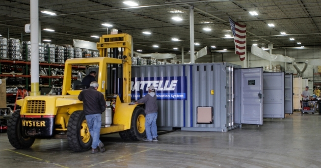 Workers inside a West Side warehouse prepare Battelle's decontamination units for deployment.