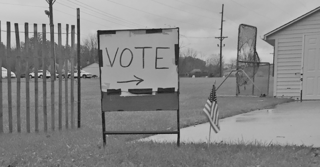 A hand-drawn sign points to a polling place.
