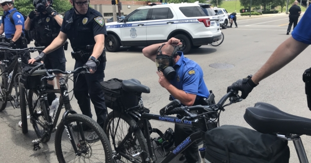 A police officer puts on a gas mask near the entrance to U.S. 35