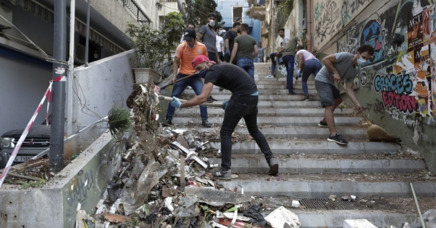 People clean up after a massive explosion in Beirut, Lebanon, Aug. 5. The blast rocked downtown Beirut on Tuesday, flattening much of the port, damaging buildings and blowing out windows and doors as a giant mushroom cloud rose above the capital. Witnesses saw many people injured by flying glass and debris. [Hassan Ammar / AP]