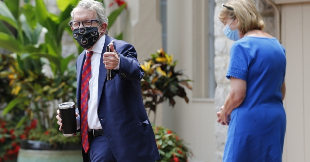 Ohio Gov. Mike DeWine, left, and his wife Fran, walk into their residence after he tested positive for COVID-19 earlier in the day. The governor's second coronavirus test of the day came back negative. [Jay LaPrete / AP]