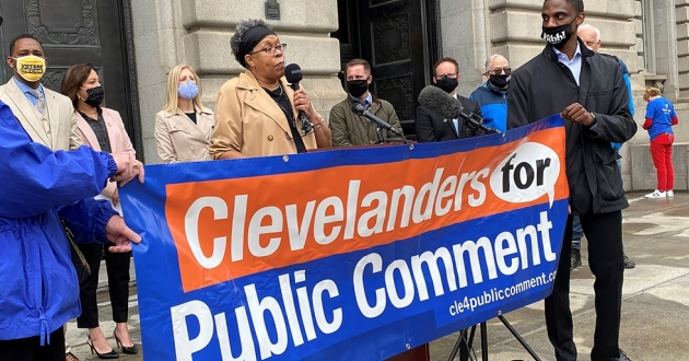 Michelle Jackson of Clevelanders for Public Comment addresses reporters from the steps of city hall Monday, along with seven city council members. [Nick Castele / ideastream]