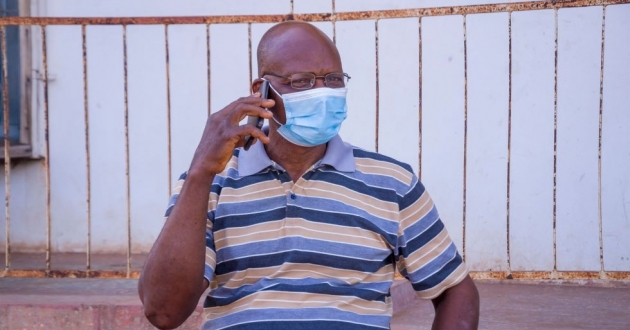 A man on a cell phone with a mask during the pandemic.