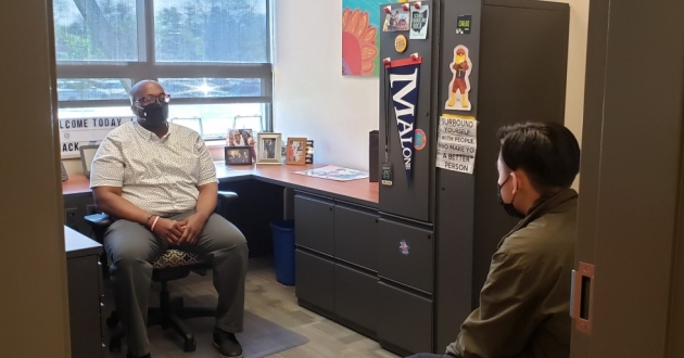 Rashawn McCraney (left) meets with a student in his office at Firestone Community Learning Center in Akron. School counselors like McCraney have had to adjust to meet students unique mental health challenges during the COVID-19 pandemic. [Rashawn McCraney]