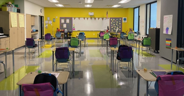 An empty classroom at Campus International School is set up with six feet between desks