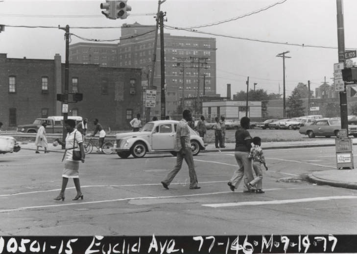 A busy intersection at E. 105th Street and Euclid Ave. in Cleveland showing African-American pedestrians and a car, 1969.