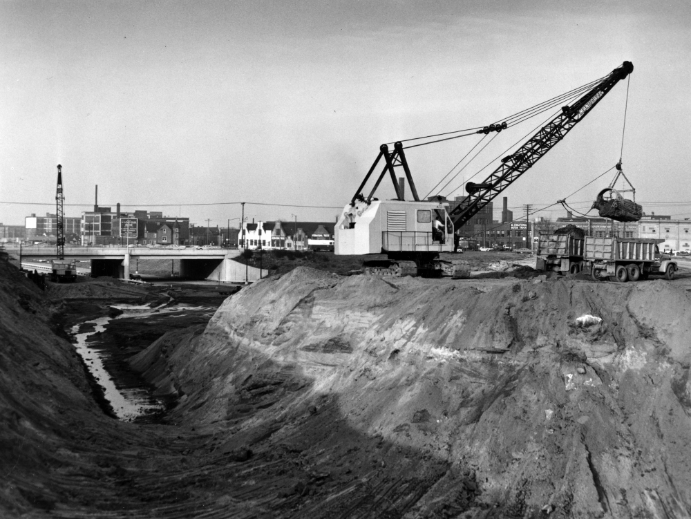 A crane loads dirt into a dump truck next to a huge ditch created for the Innerbelt Highway, 1960.