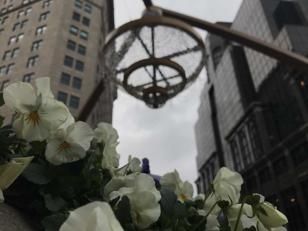 The GE chandelier, with an overcast sky behind it and white pansies in the foreground, at Playhouse Square, May 14, 2019.  [Amy Eddings / ideastrem]