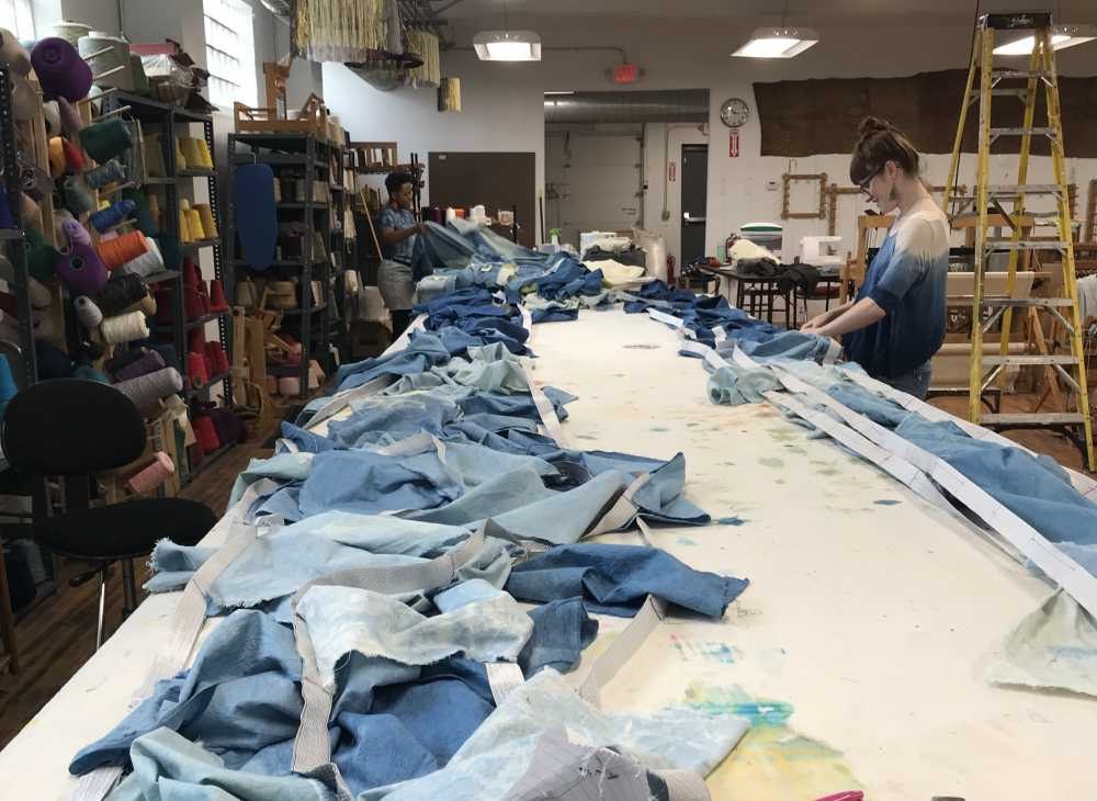 Volunteers stitch together hundreds of indigo-dyed cotton squares into banners at Praxis Fiber Workshop in North Collinwood, June 6, 2019t. The three banners will be installed at the Detroit Superior Bridge starting today. [Jessica Pinsky]