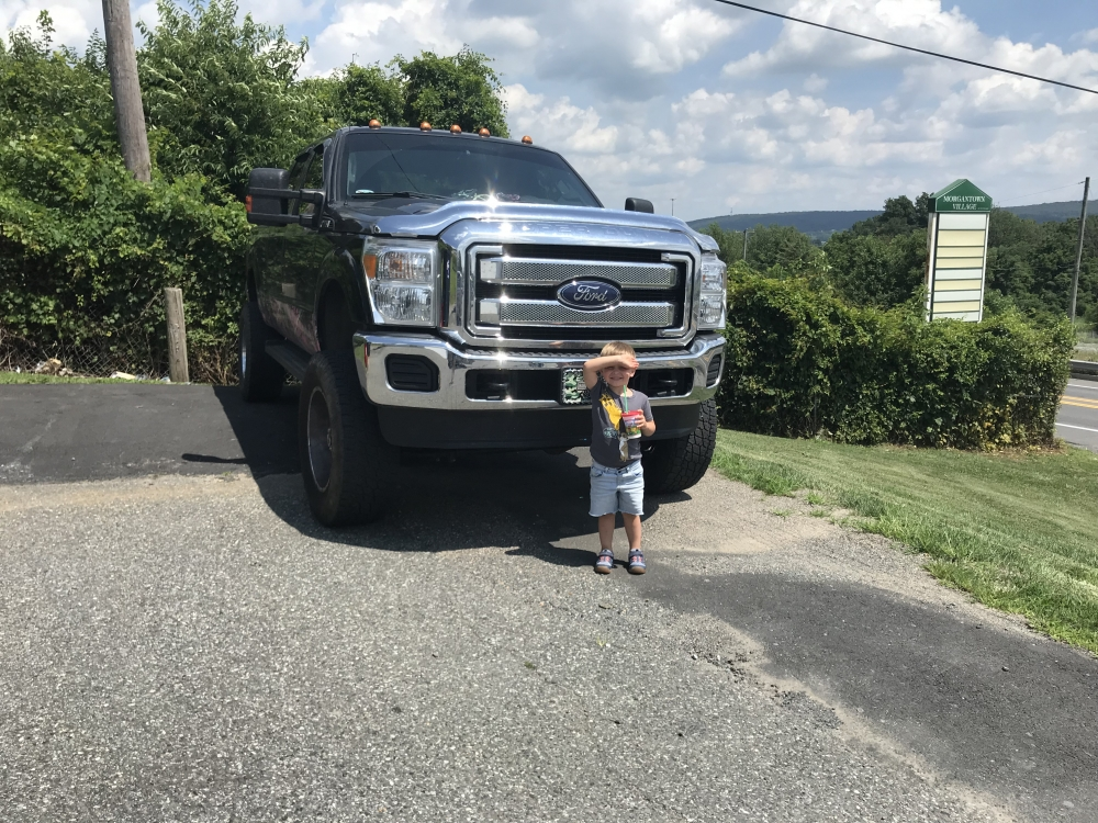 Angie Schmitt's four-year-old son is dwarfed by the high front end of a Ford F250. [Angie Schmitt]
