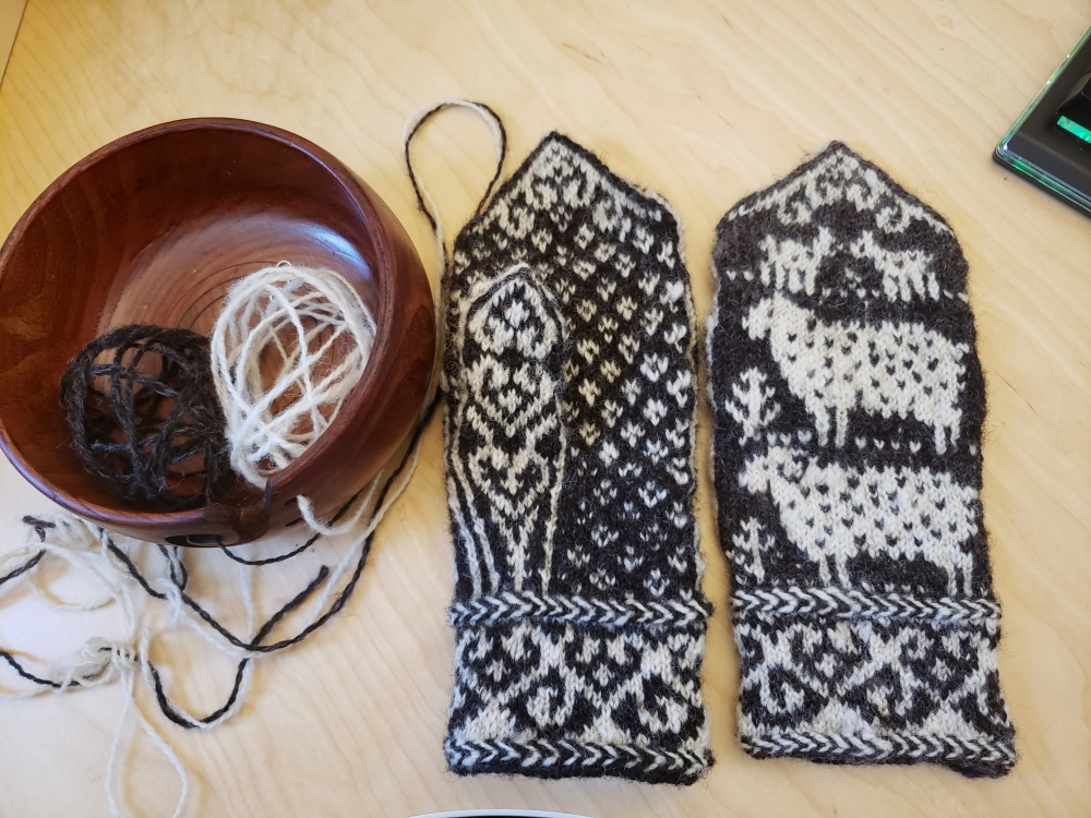 Two black and white mittens knit with sheep wool in an Icelandic pattern.