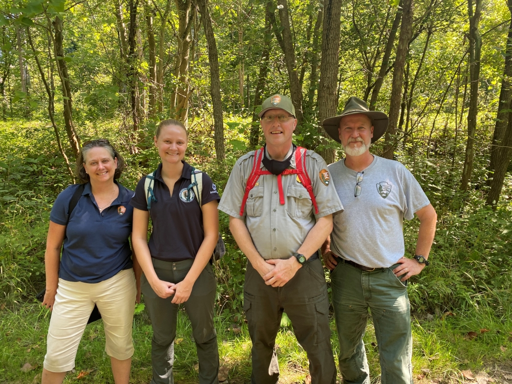 Public relations director Pamela Barnes, volunteer coordinator Cami Miller, Park Ranger Josh Bates and ecologist Chris Davis of the Cuyahoga Valley National Park stand together in front of a stand of leafy green trees.