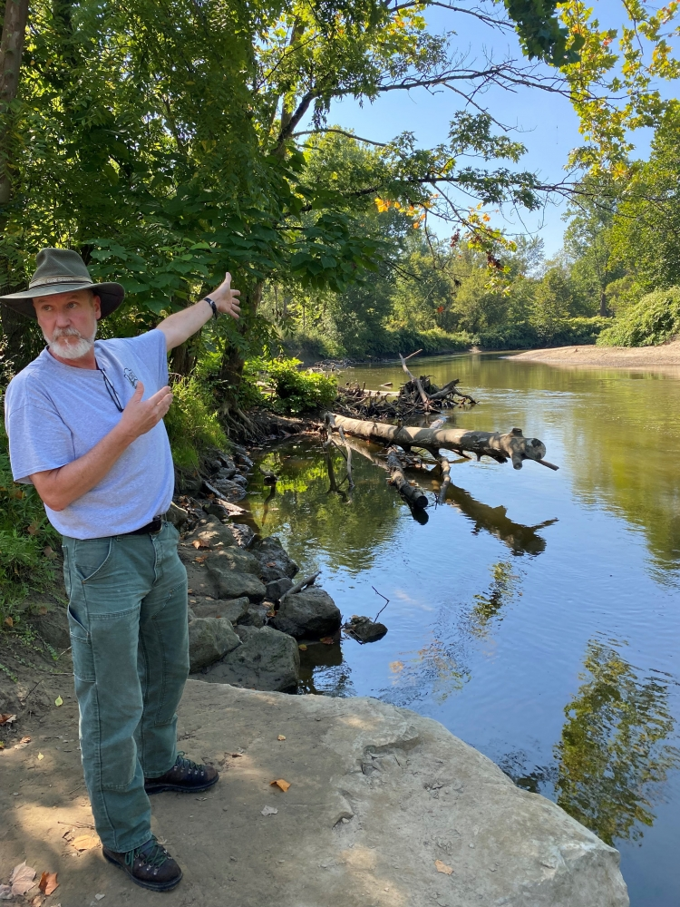 Cuyahoga Valley National Park ecologist Chris Davis, standing on the bank of the Cuyahoga River, points upriver past large trees and fallen logs to a spot in the river where engineers eliminated a large meander bend in the river.