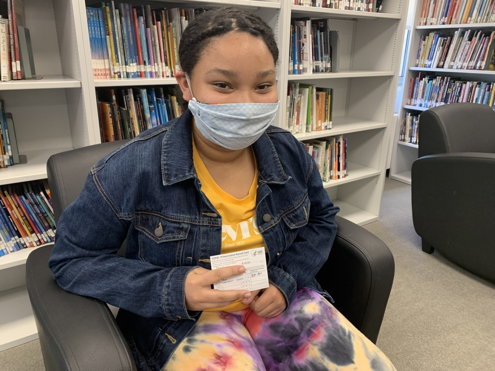 Seventh grader Kiessa Brown poses with COVID vaccine card