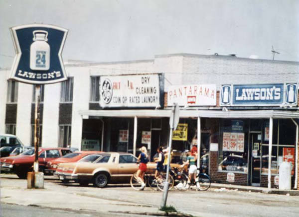 "A picture of a Lawson's store in 1980. A sign with a milk can and the words ""Lawson's"" appears on the left and right, and a few kids are walking with their bikes in the parking lot in front of the store."