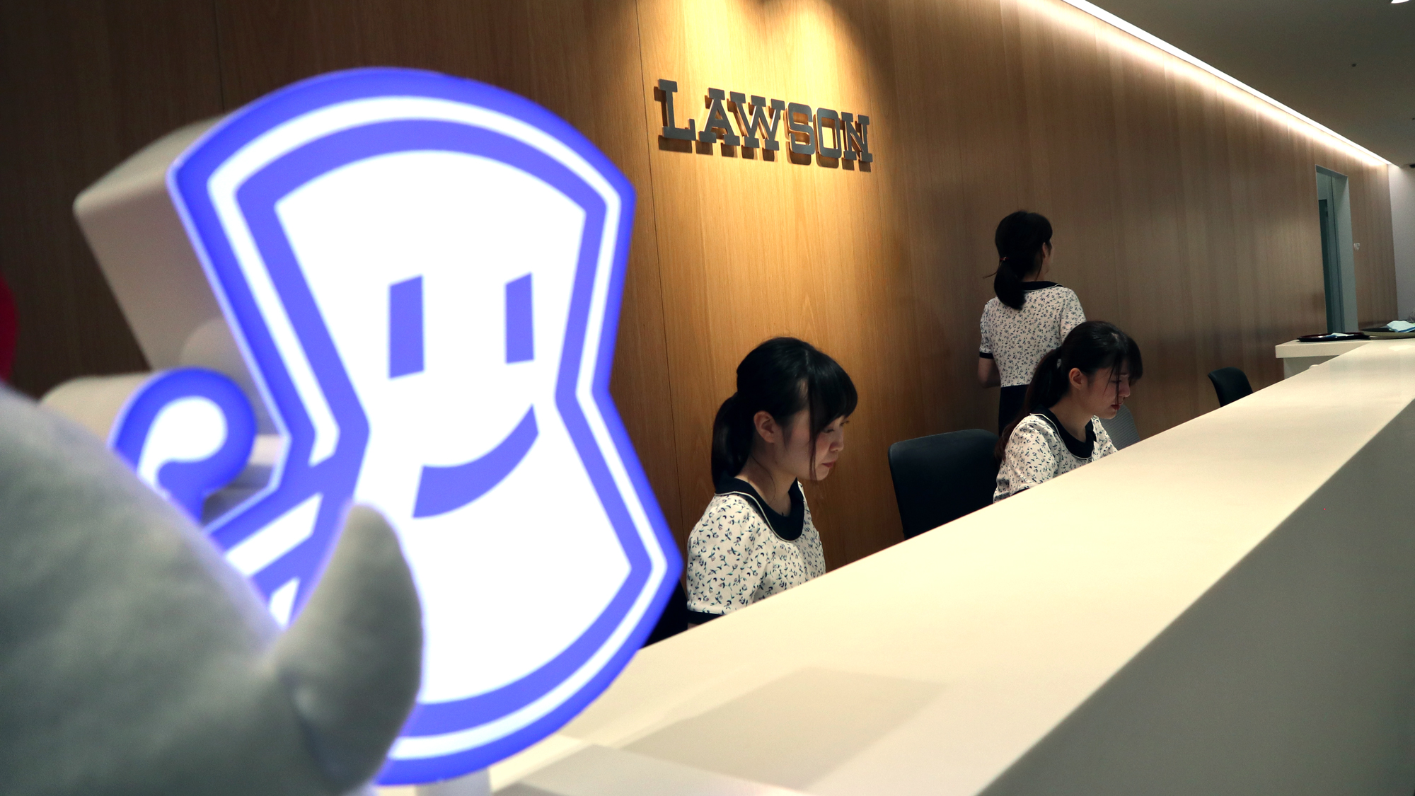 The front lobby of Lawson company headquarters in Tokyo. A cartoon version of the Lawson emblem sits on a long white counter. Three women wearing matching black and white dresses sit behind the counter.