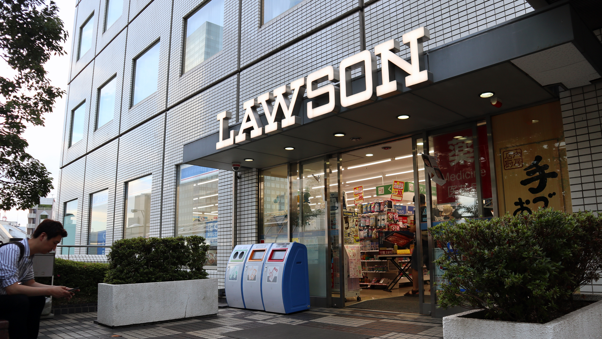"A Lawson store near the company's HQ in Tokyo's Ōsaki neighborhood. The name ""Lawson"" appears across the awning in bright white letters, in the same old-timey font as the original Lawson store from Ohio."