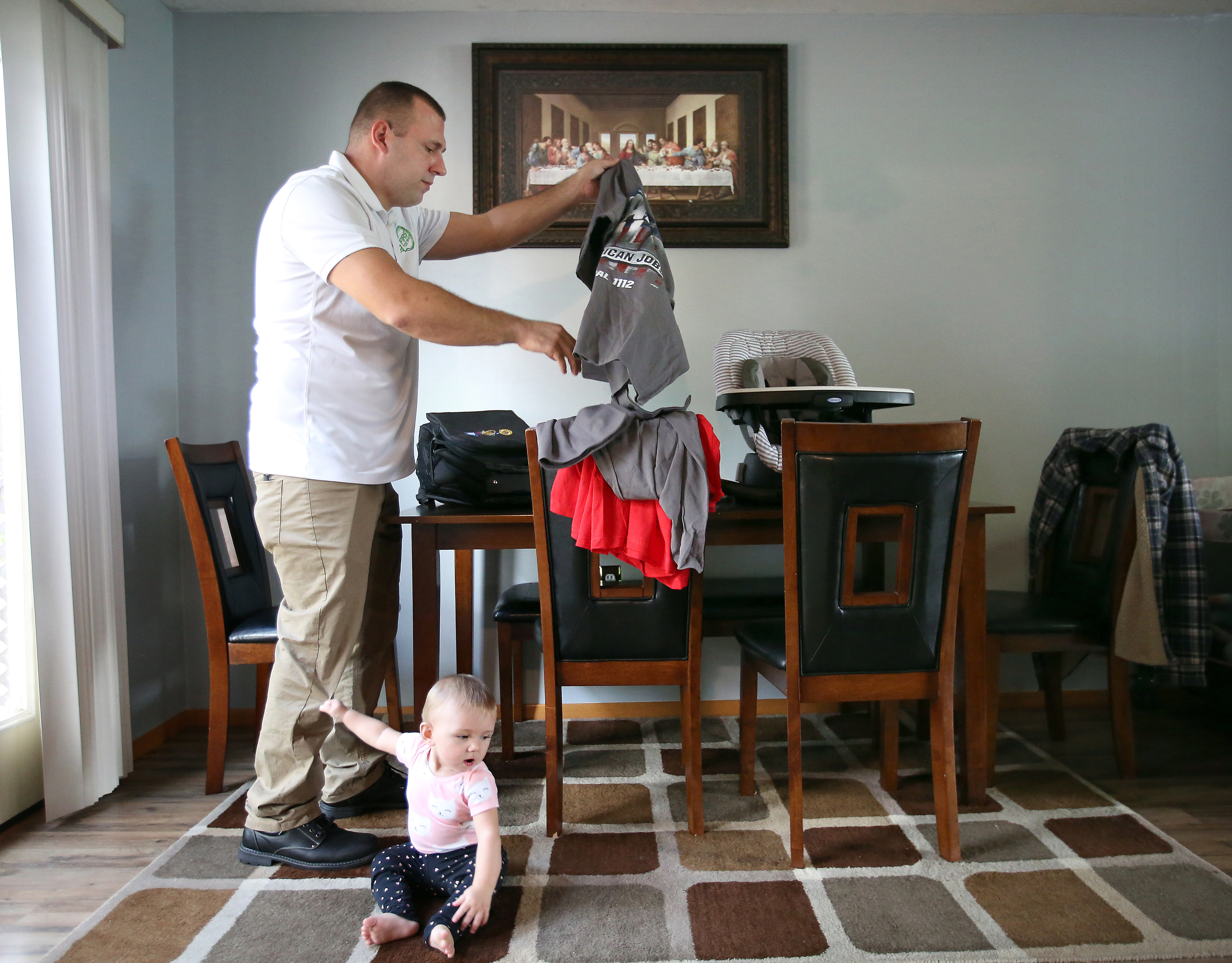 Tommy Wolikow packs alongside his nine-month-old daughter