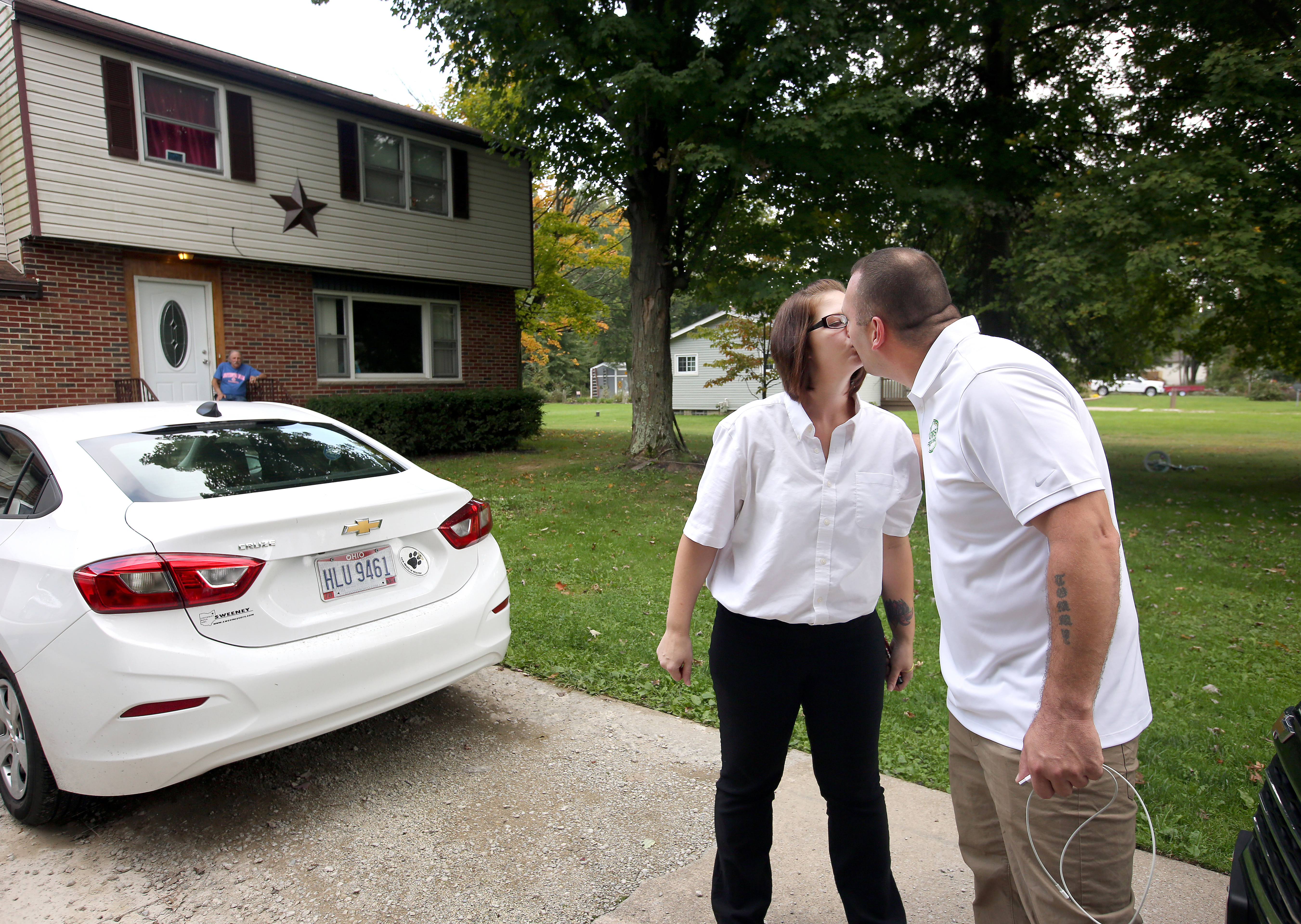 Tommy Wolikow and Rochelle Carlisle kiss outside their home in Warren