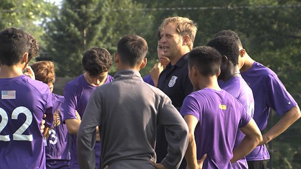 Coach Andrew Toth huddles with his Lakewood High School soccer team.