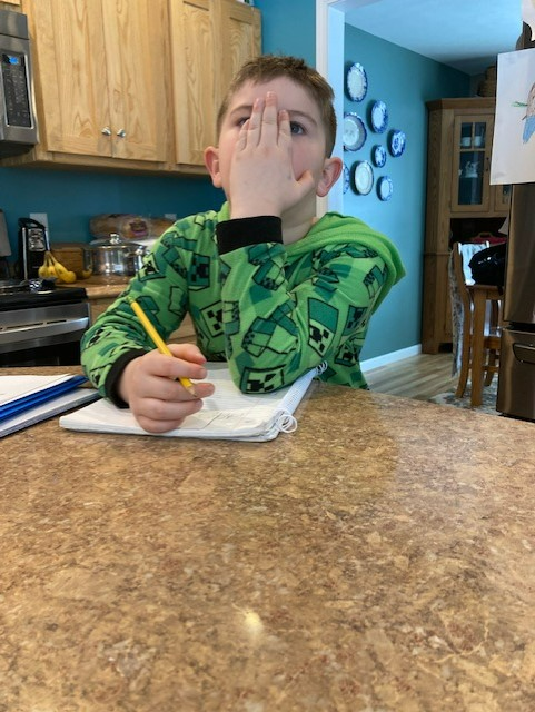 Jessica Schillace's son with palm on his face as he holds a pencil in his other hand.