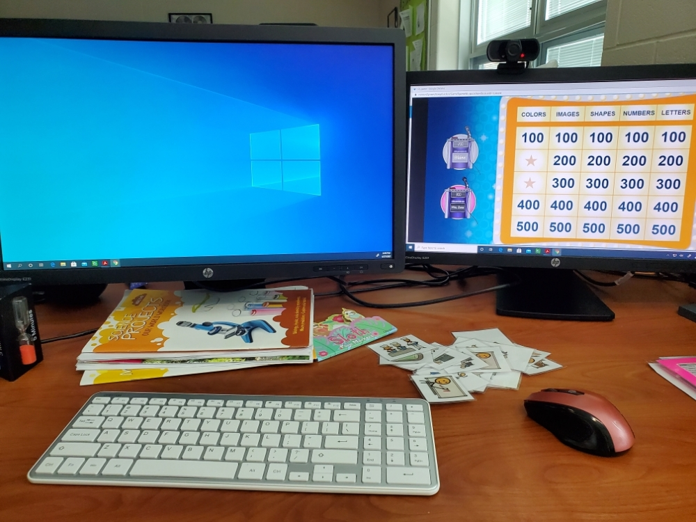 Two computer screens and some picture cards on a desk.