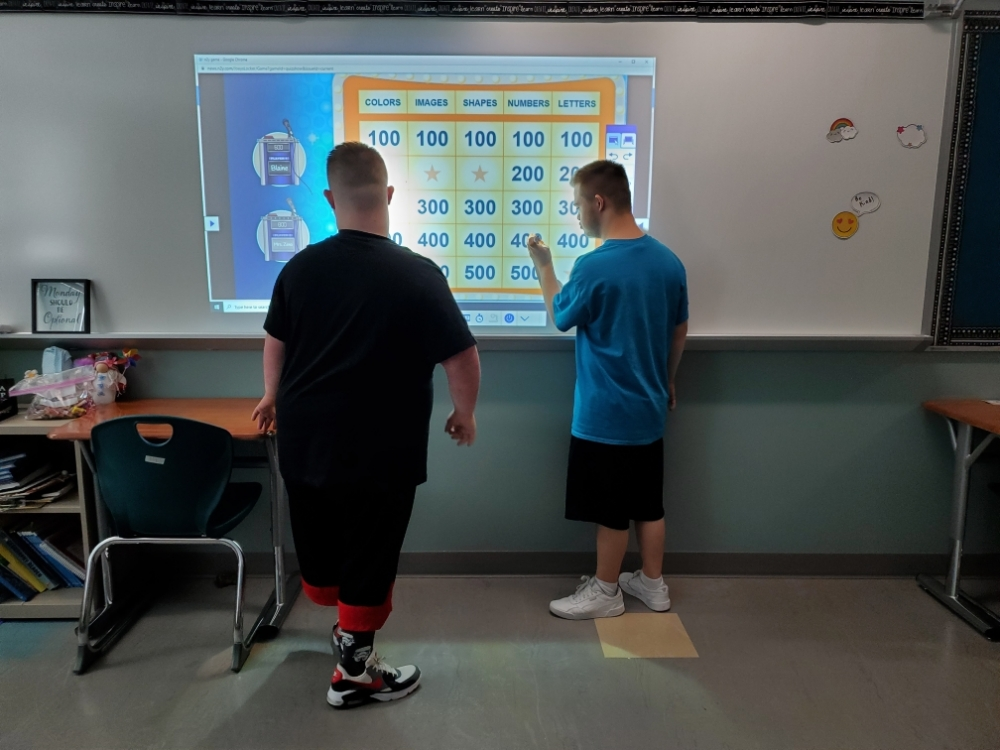 Ellet High School Students Blaine Smith and Kyle Bolinger play an educational game on a smart board.