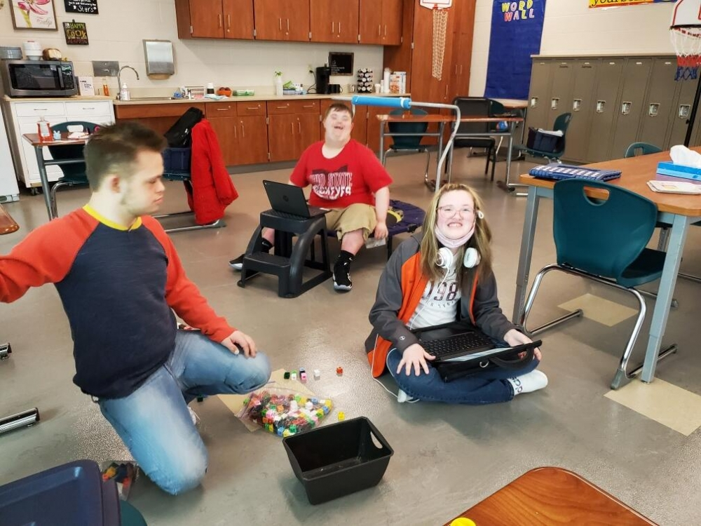 Three kids working on a classroom floor