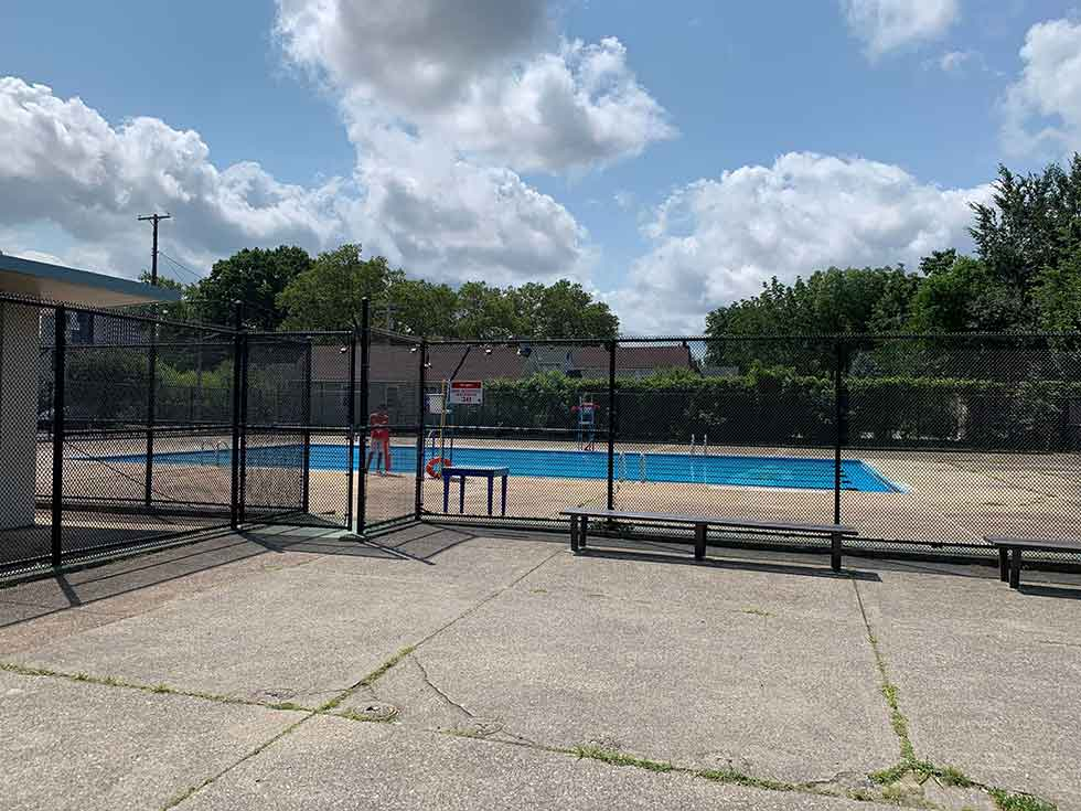 A public pool surrounded by concrete and a chain link fence in Cleveland's Clark-Fulton neighborhood.