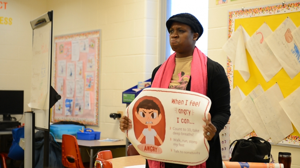 Teaching artist Andrea Belser makes an angry face while teaching kids about anger.