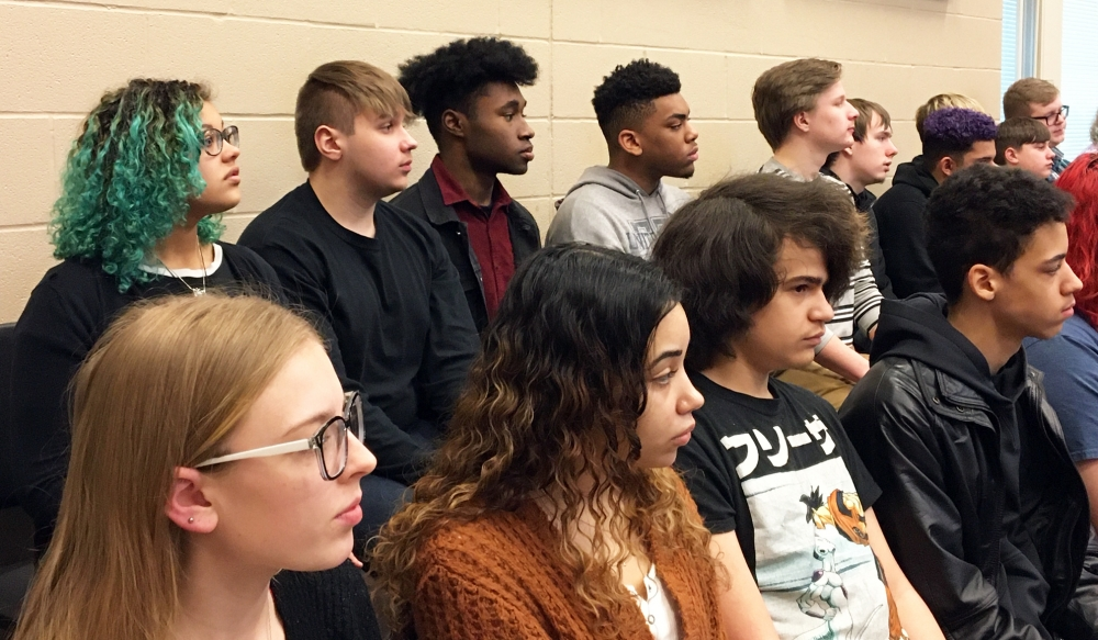 Students in the a cappella choir listen to direction from Lester Lynch. 12th grader Tyjaon Grantham (wearing red shirt in back row) was interested in hearing about Lynch's experiences.